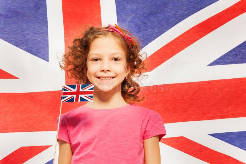 Fille drôle avec peu de drapeau contre la bannière britannique images libres de droits