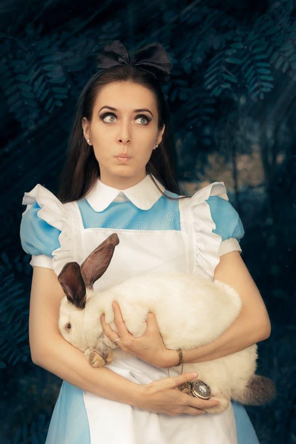Fille drôle costumée comme Alice au pays des merveilles avec le lapin blanc photographie stock libre de droits
