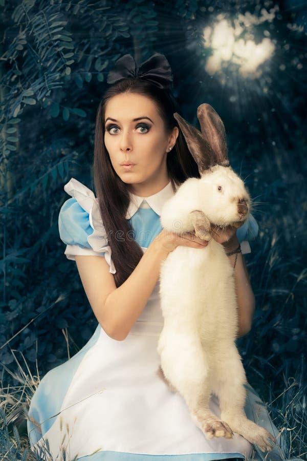 Fille drôle costumée comme Alice au pays des merveilles avec le lapin blanc images stock