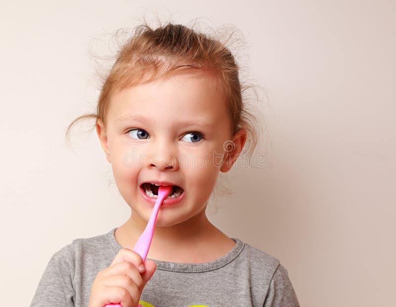 Fille drôle d'enfant brossant les dents photo stock