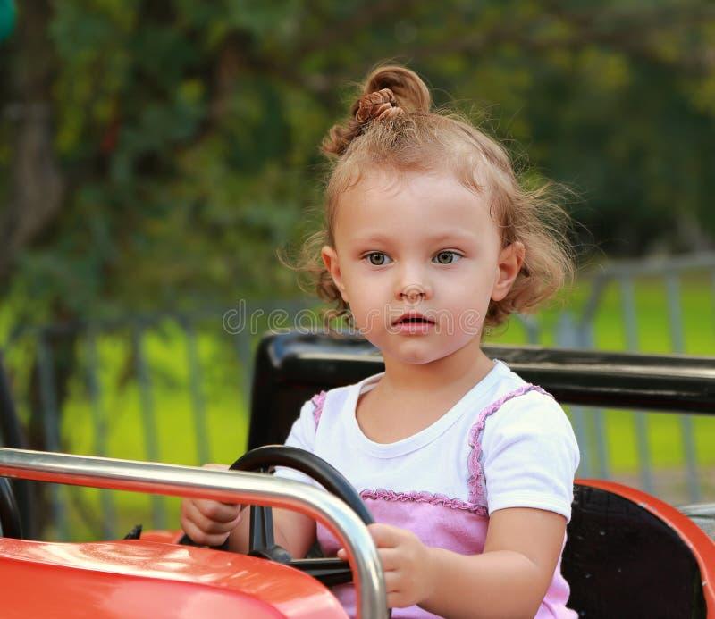Fille drôle d'enfant conduisant la voiture photographie stock libre de droits