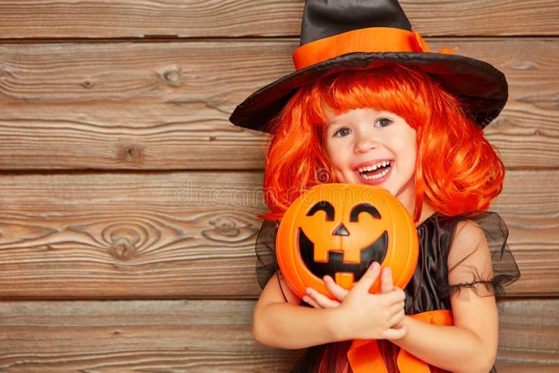 Fille drôle d'enfant dans le costume de sorcière pour Halloween avec le potiron Ja photo stock