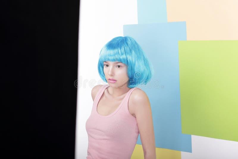 Fille drôle dans la perruque bleue de fantaisie et le singulet rose image libre de droits