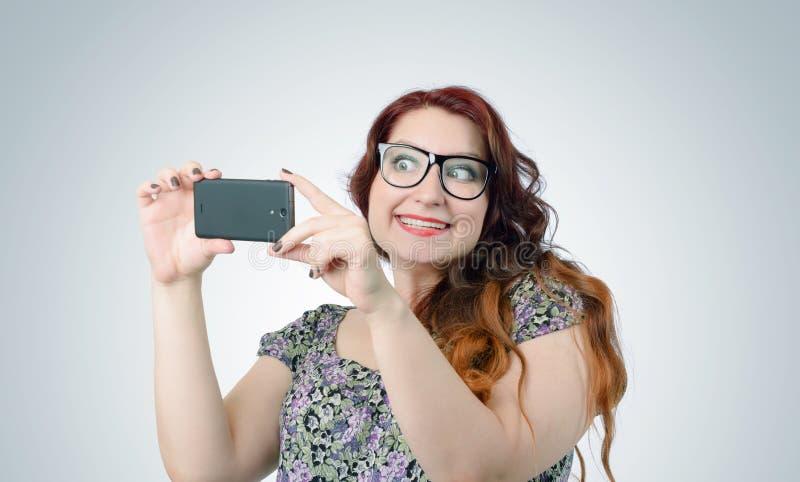Fille drôle de vipère avec un smartphone sur le fond photographie stock