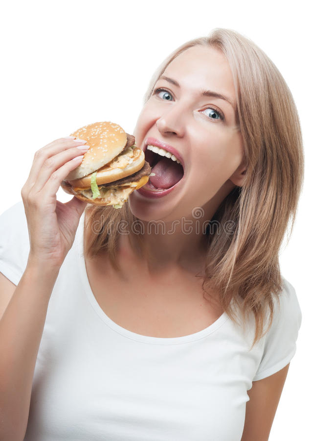 Fille drôle mangeant l'hamburger d'isolement sur le fond blanc photo stock