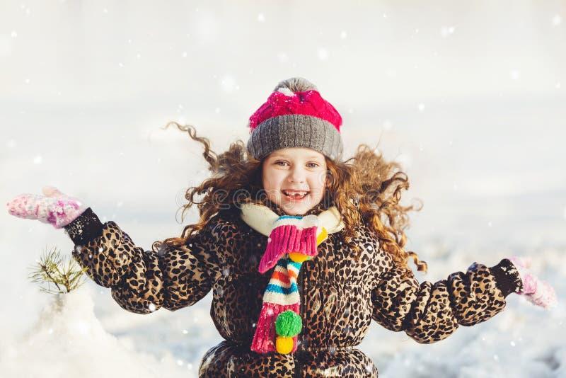 Fille drôle vers le haut de sa main, et flocons de neige en baisse de crochets Enfance heureux et concept sain images stock