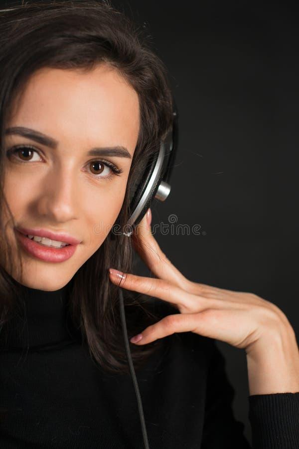 Fille du DJ dans des battements de écoute de disco d'écouteurs posant dans le studio au-dessus du fond foncé Jeune modèle caucasi photo stock