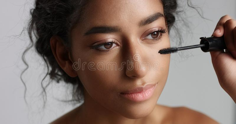 Fille du Moyen-Orient adolescente adorable avec la grande peau appliquant le mascara à ses longues mèches photos libres de droits
