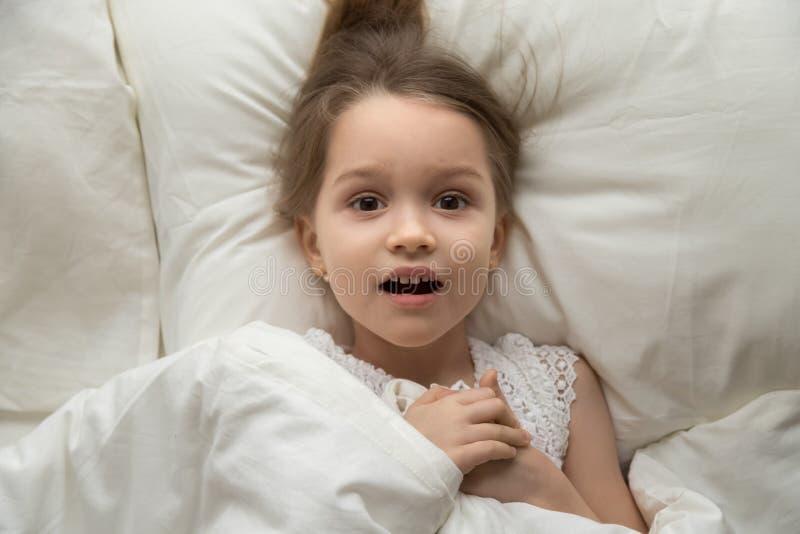 Fille effrayée par vue ci-dessus se trouvant sur le lit regardant la caméra images libres de droits