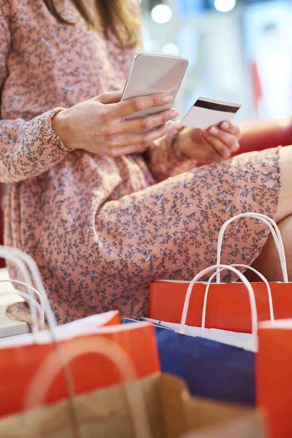 Fille employant le téléphone portable et la carte de crédit pendant des achats en ligne photo libre de droits