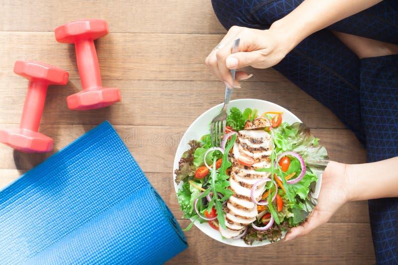 Fille en bonne santé de vue supérieure mangeant de la salade de poulet Haltères et tapis de yoga sur le plancher photographie stock