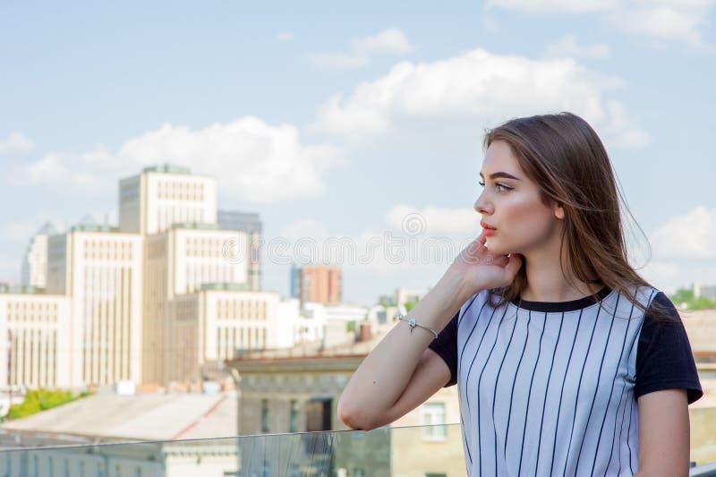 Fille en bref sur le balcon dans un café Portrait d'été de la jeune fille élégante posant sur le balcon, mini shorts de denim image libre de droits