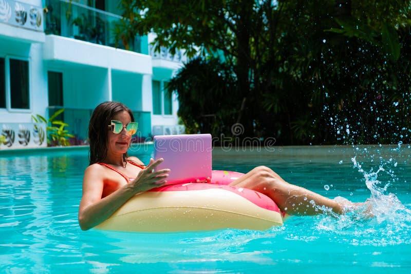 Fille en cercle gonflable dans la piscine avec un ordinateur portable, concept de travailler en ind?pendant et r?cr?ation photographie stock
