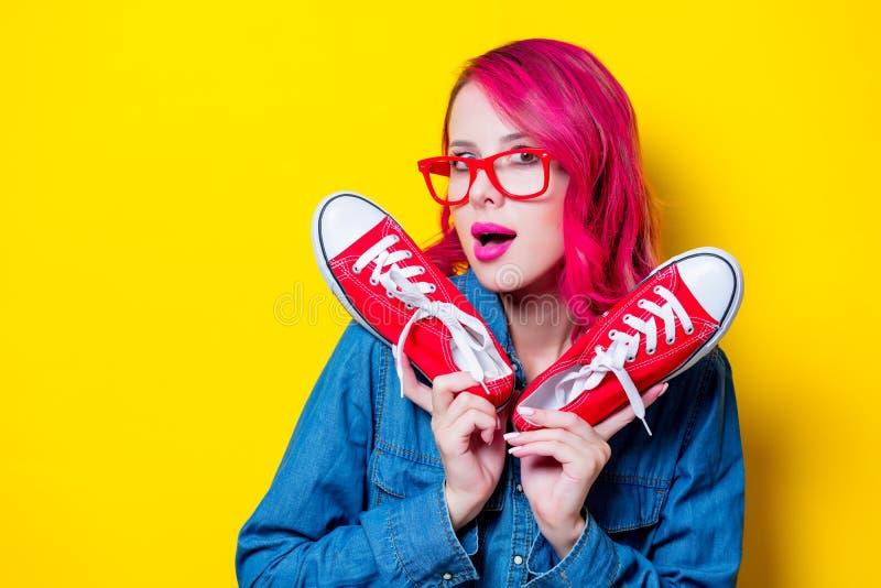 Fille en chemise bleue et verres tenant des chaussures en caoutchouc photographie stock