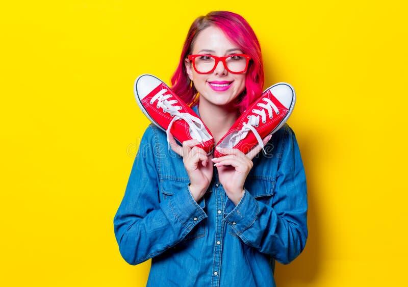 Fille en chemise bleue et verres tenant des chaussures en caoutchouc photos stock