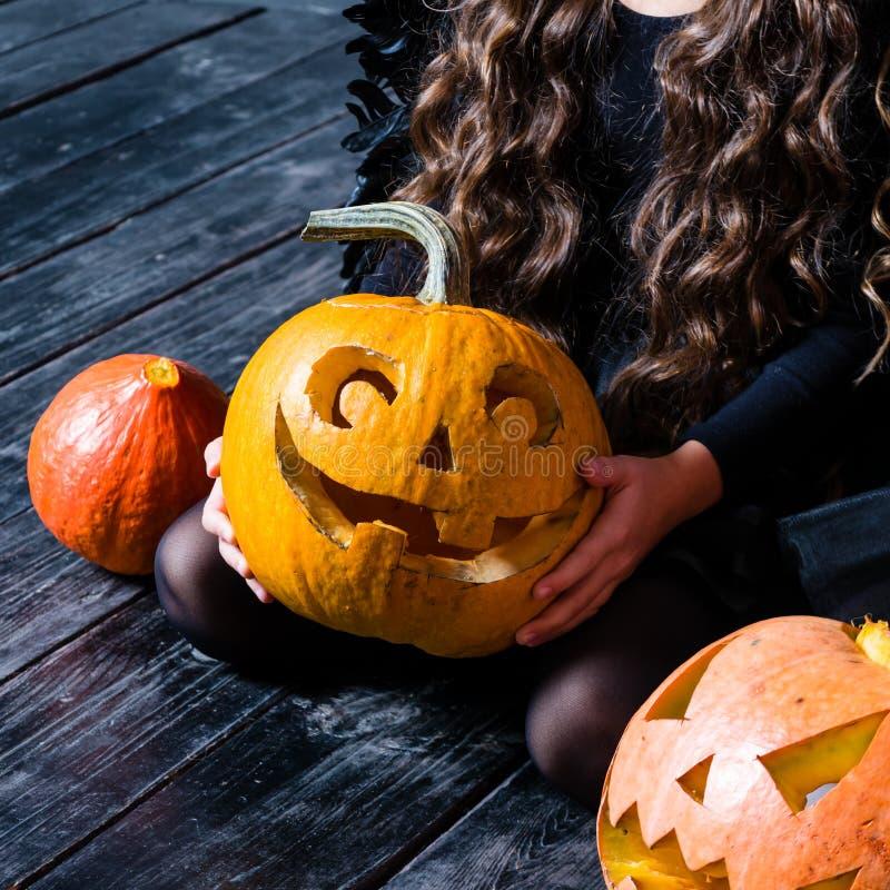 Fille en gros plan tenant la lanterne de cric de tête de potiron de Halloween dessus image libre de droits