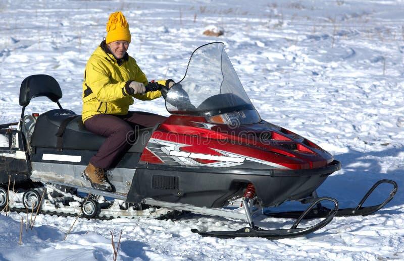 Fille en jaune sur le scooter de neige photos stock