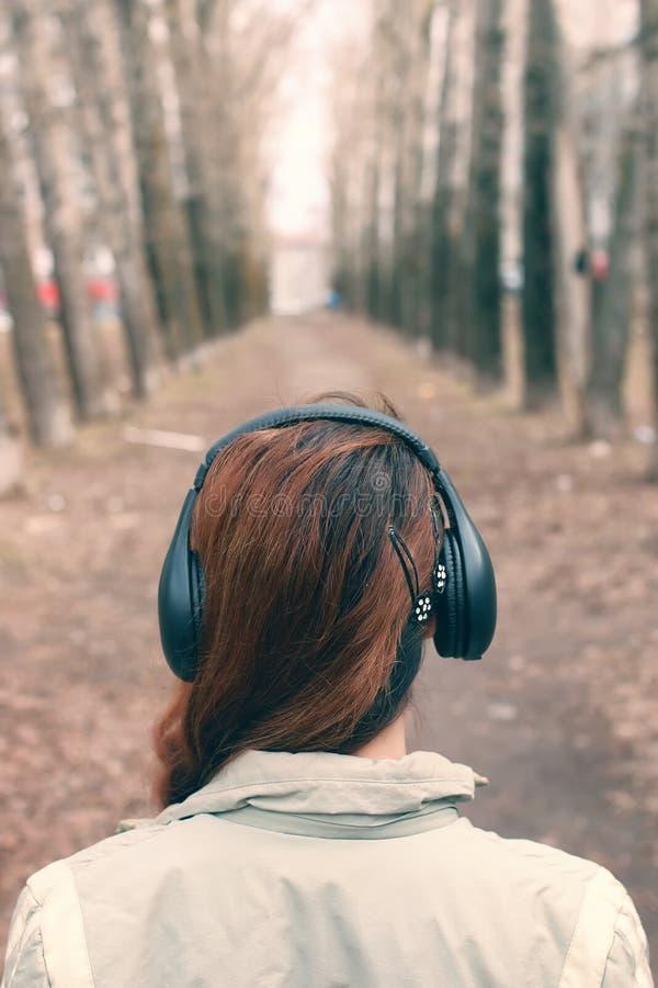 Fille en parc avec l'écouteur photos libres de droits