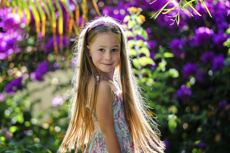 Fille en parc parmi des fleurs photos stock