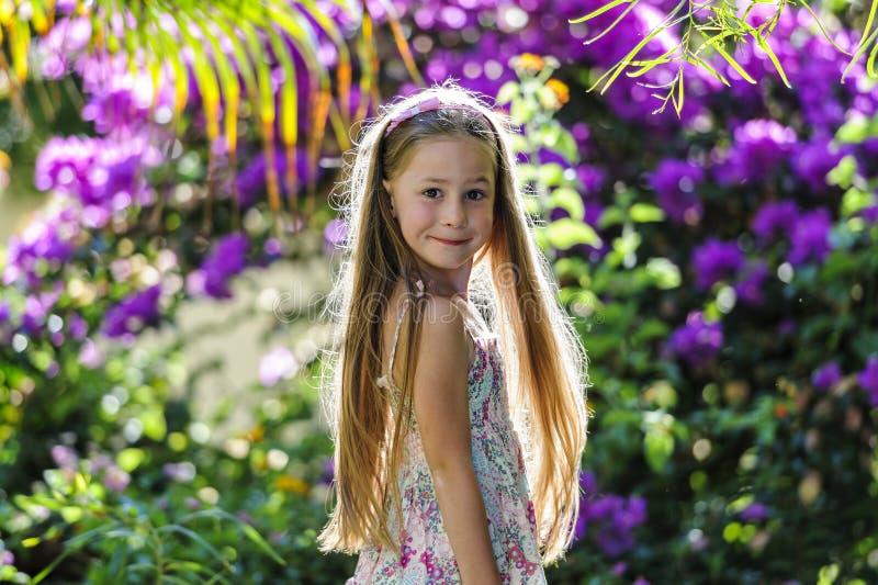 Fille en parc parmi des fleurs images libres de droits