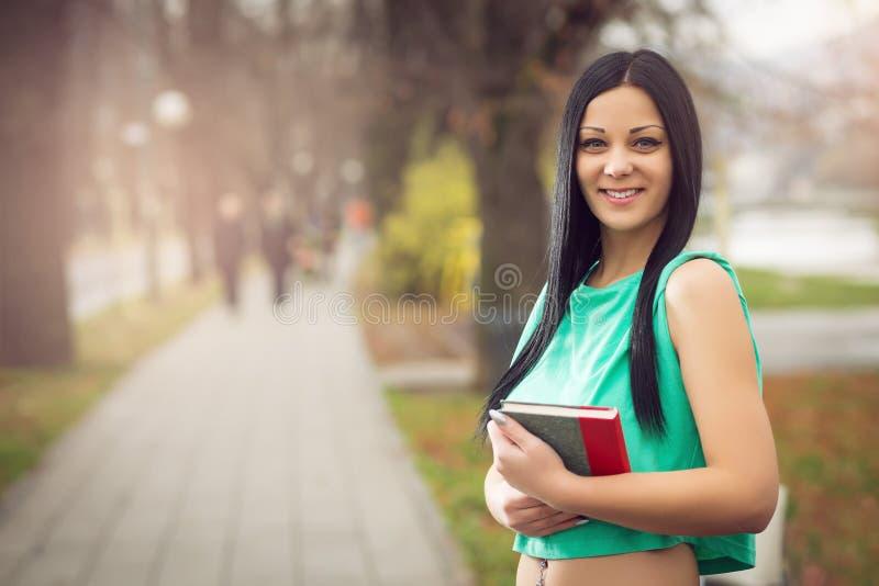 Fille en parc tenant le livre image stock