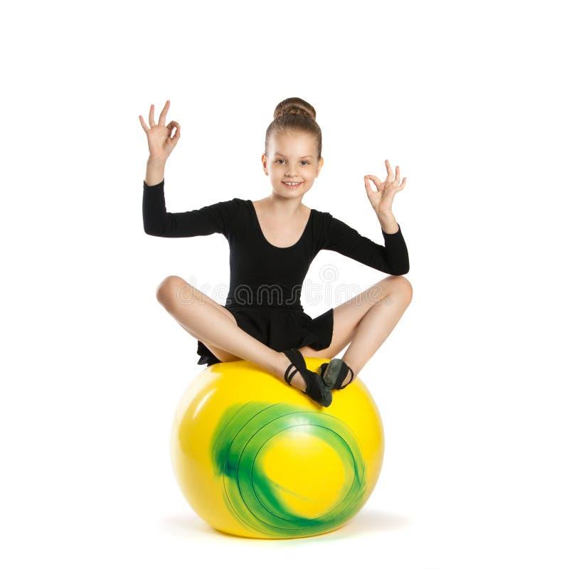 Fille en position de lotus sur un grand ballon jaune photo libre de droits