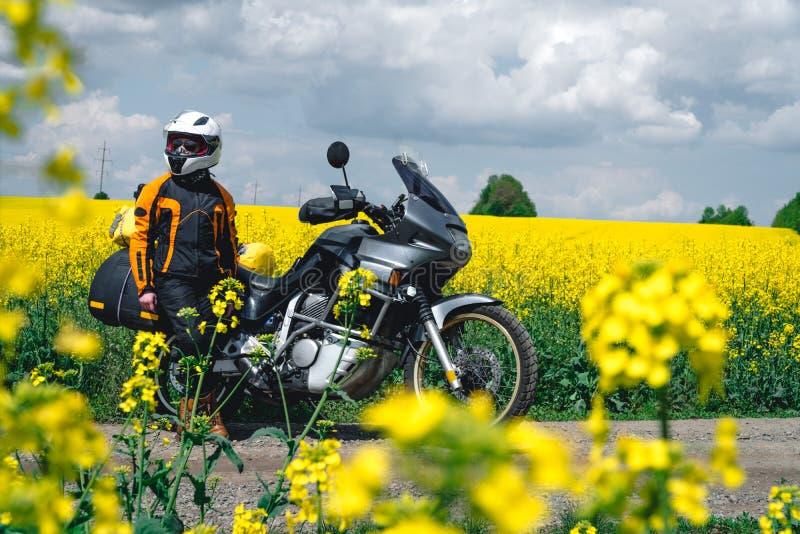 Fille en ?quipement et verres de protection avec la moto touristique Gisement de fleurs jaune de viol sur le fond Visite de tra?n images stock