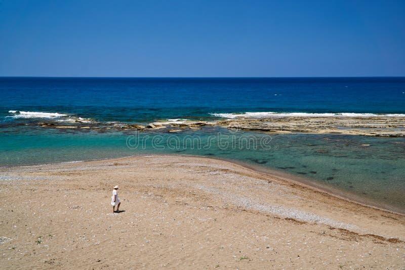 Fille en robe blanche et chapeau sur une plage rocheuse photographie stock libre de droits