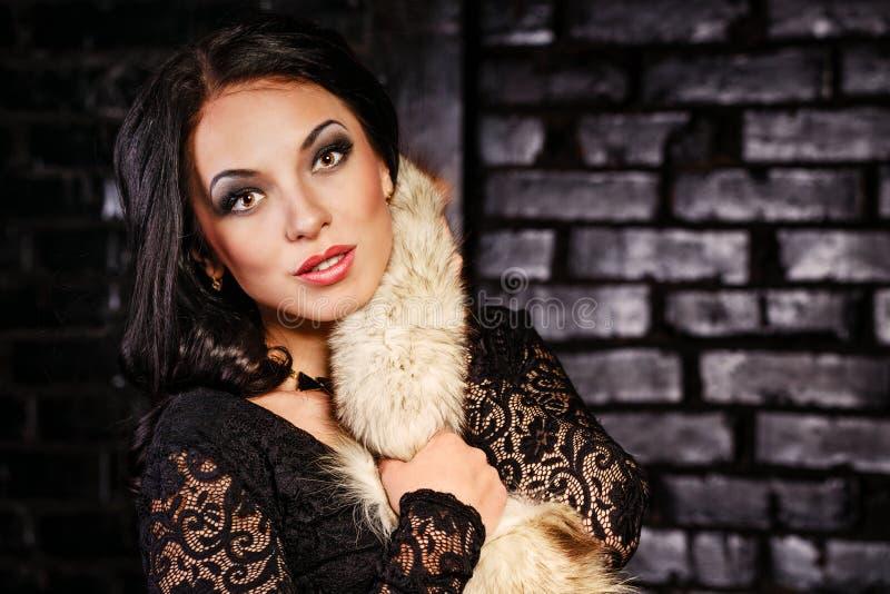 Fille en robe noire et fourrures photos stock
