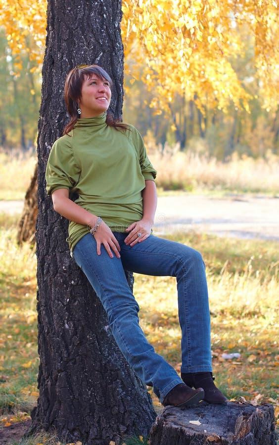 Fille en stationnement d'automne près d'arbre photo stock