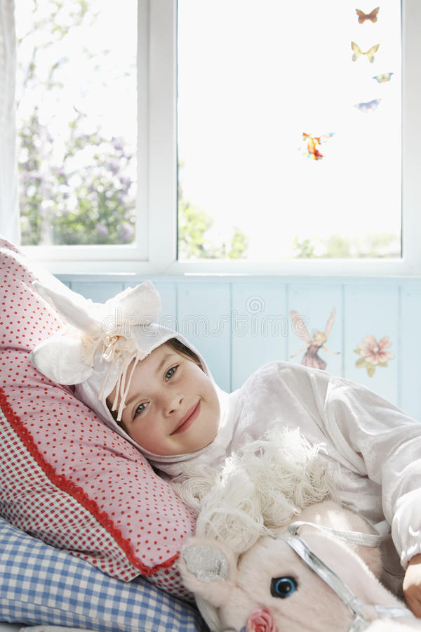 Fille en Unicorn Costume se situant dans le lit images stock