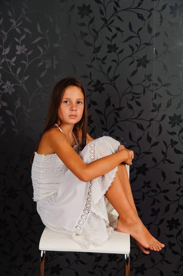 Fille en vêtements blancs assise sur une chaise en studio images stock