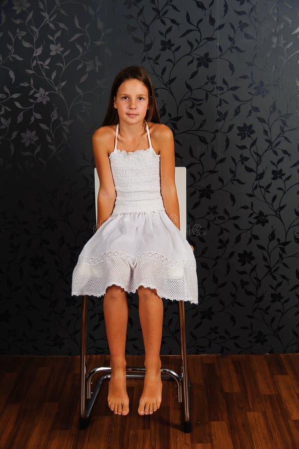 Fille en vêtements blancs assise sur une chaise en studio photos libres de droits