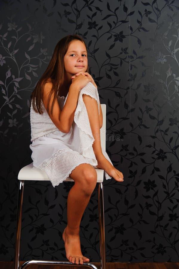 Fille en vêtements blancs assise sur une chaise en studio images libres de droits