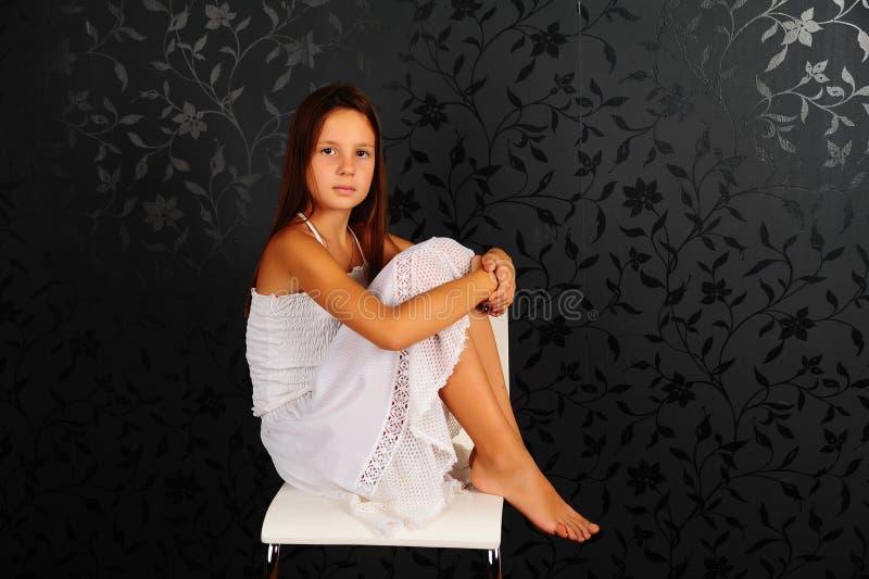 Fille en vêtements blancs assise sur une chaise en studio photos stock