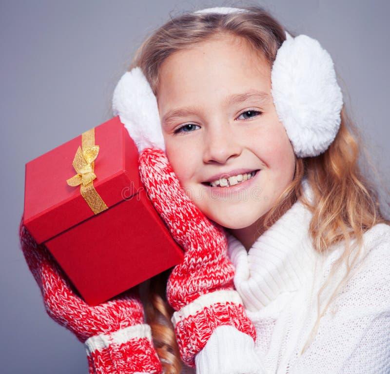 Fille en vêtements d'hiver avec cadeau photographie stock
