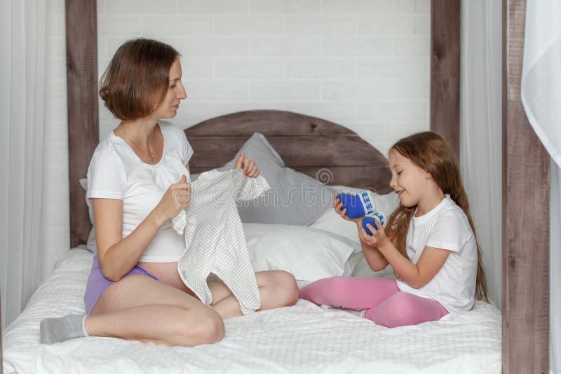 Fille enceinte de mère et d'enfant préparant l'habillement pour le bébé nouveau-né image stock