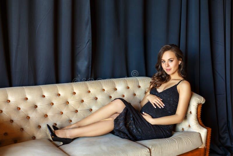 Fille enceinte s'asseyant sur le divan dans une belle robe photo stock