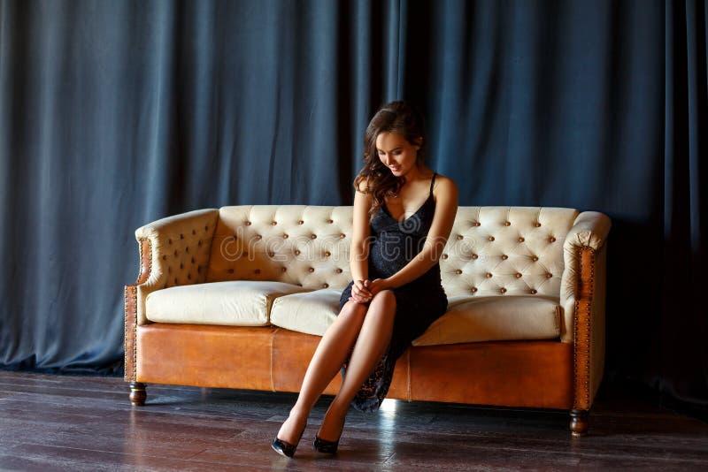 Fille enceinte s'asseyant sur le divan dans une belle robe image libre de droits