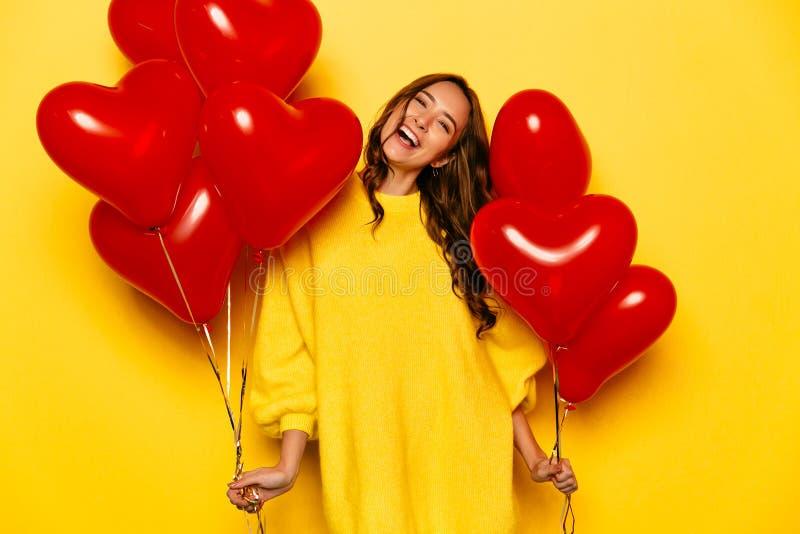 Fille enthousiaste avec les ballons à air en forme de coeur le jour du ` s de Valentine image libre de droits