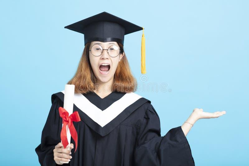 fille enthousiaste d'obtention du diplôme montrant quelque chose en main images stock