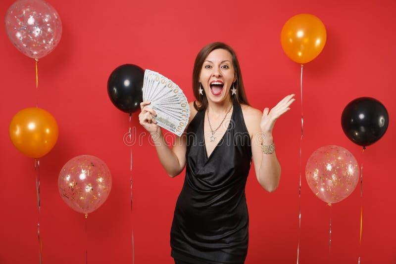 Fille enthousiaste heureuse dans la robe noire célébrant, mains de propagation, tenant un bon nombre de paquet de dollars, argent photo stock