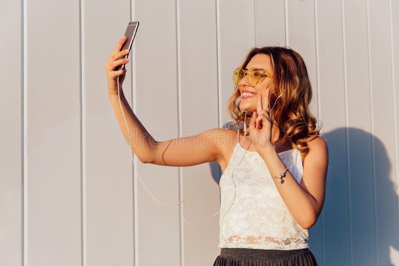 Fille enthousiaste montrant un signe de paix tout en prenant un selfie au téléphone portable photo libre de droits