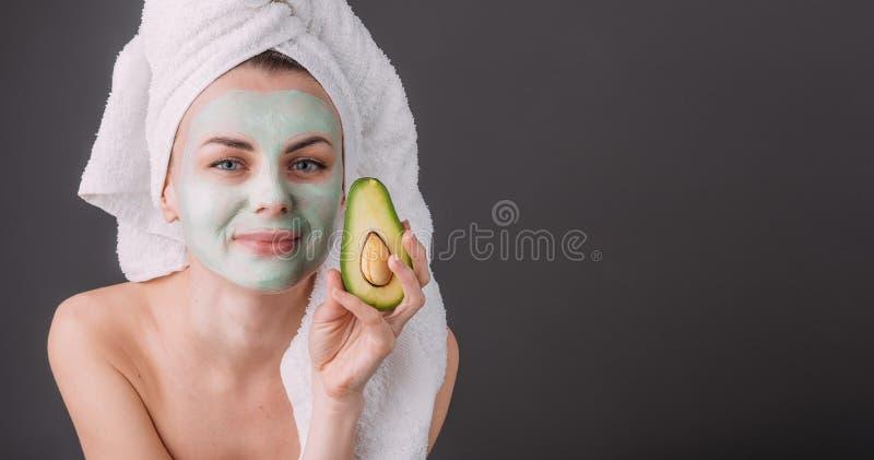 Fille enveloppée en serviette avec un masque cosmétique sur son visage et avocat dans des ses mains photographie stock libre de droits