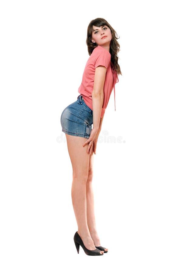 Fille espiègle dans la mini jupe de jeans. D'isolement photographie stock libre de droits