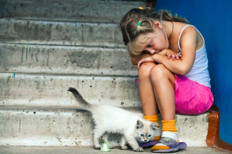 Fille et chat s'asseyants photos stock