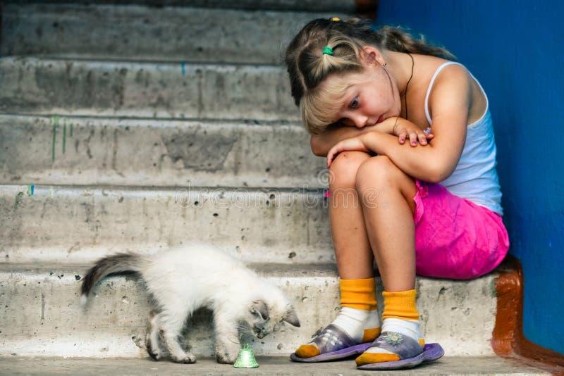 Fille et chat s'asseyants photographie stock