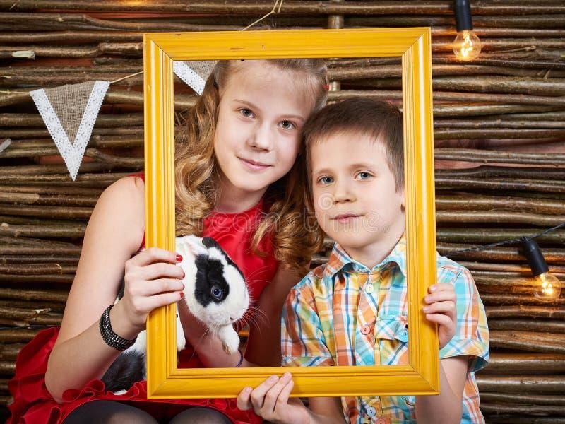 Fille et garçon avec le lapin dans le cadre de la photo images stock