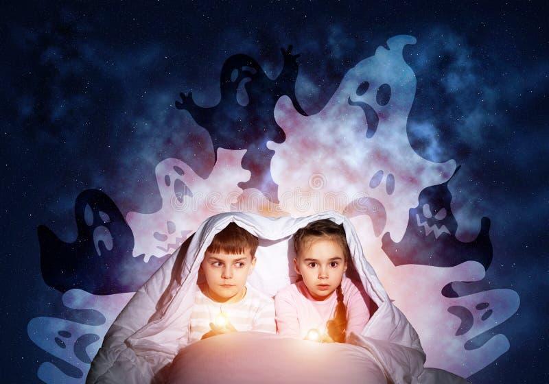 Fille et garçon effrayés avec le flashlighst image stock