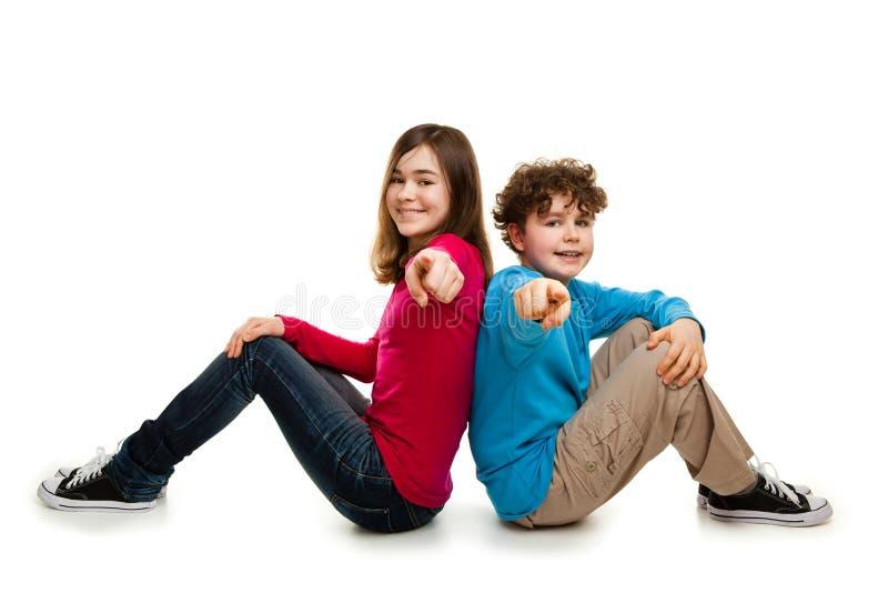 Fille et garçon s'asseyant et se dirigeant sur le fond blanc images stock